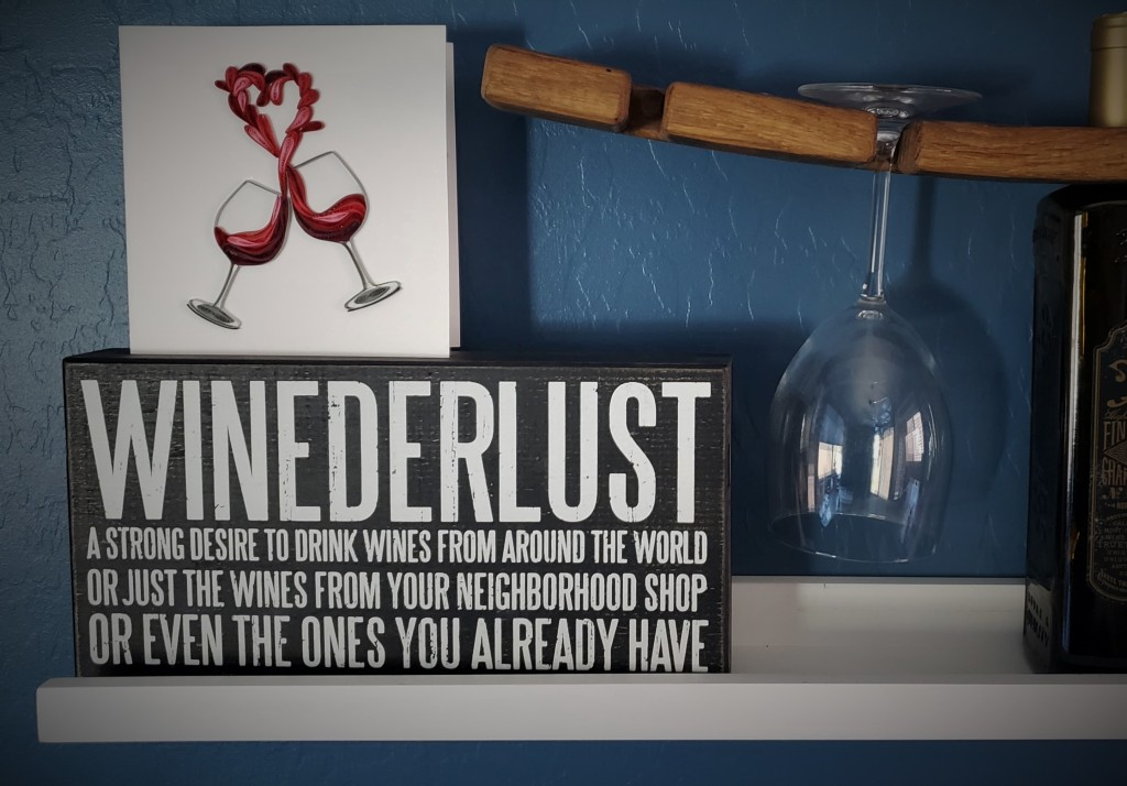 """Sign on a wall: """"Winederlust - a strong desire to drink wines form around the world or just the wines from your neighborhood shop or even the ones you already have."""" Photo also shows a decorative card with wine glasses and wine shaped in the shape of a heart."""