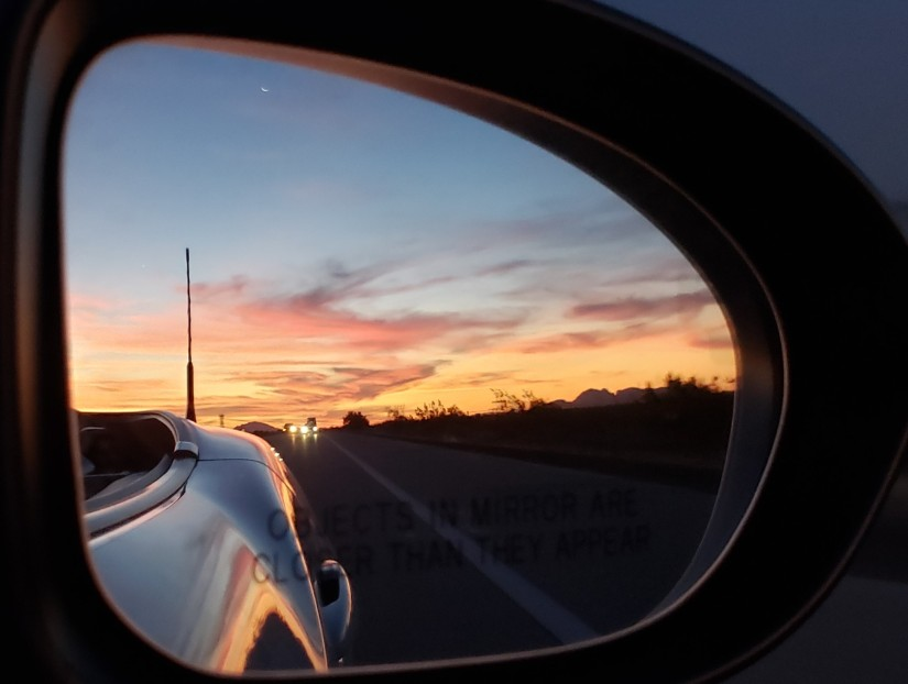 sunset in car rearview mirror