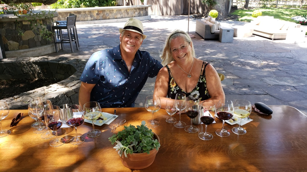 couple smiling sitting at a table set for a wine tasting under a shade tree