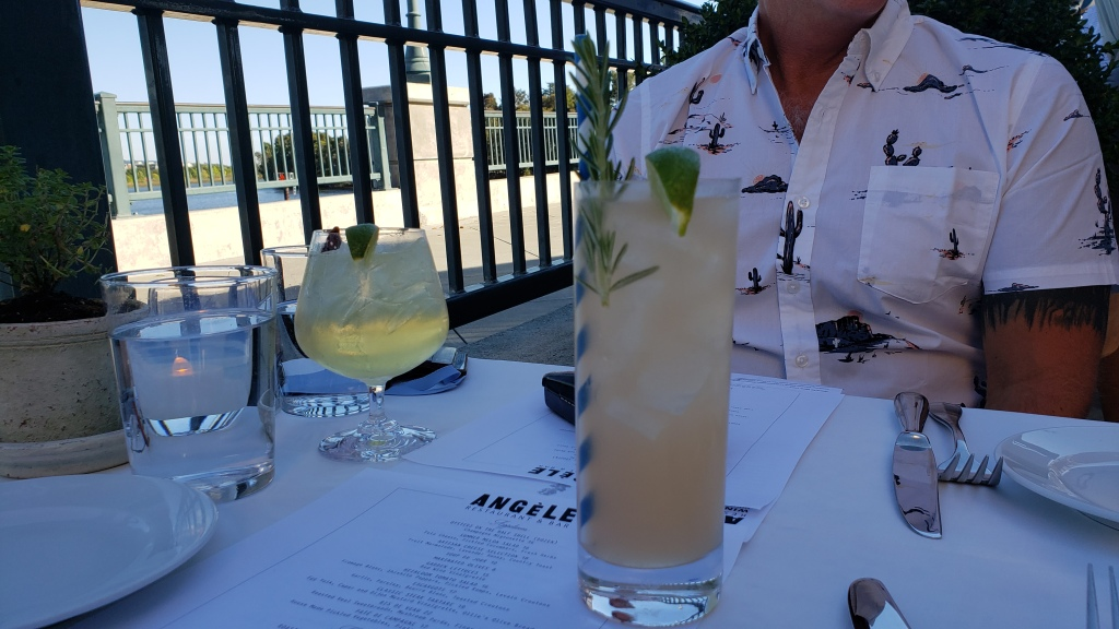 cocktails on a table with riverwalk scene beyond