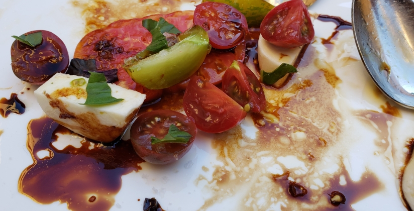 brightly colored heirloom tomatoes, fresh mozzarella cheese and balsamic vinegar