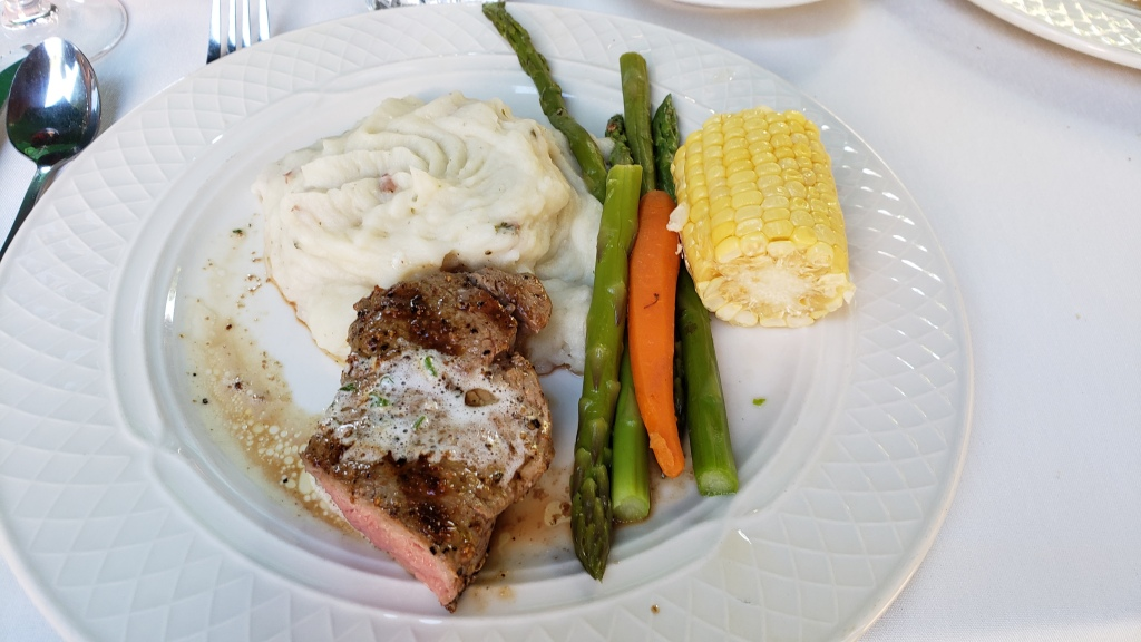 Steak smothered in butter with asparagus, corn and carrots and a pile of garlic mashed potatoes.