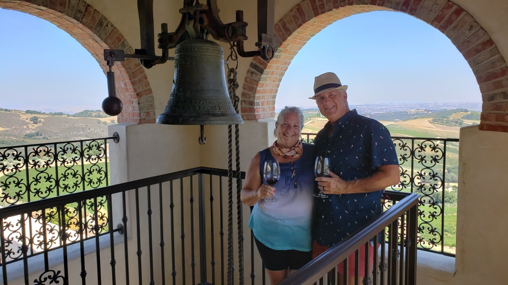 Couple holding wine glasses near bell in bell tower