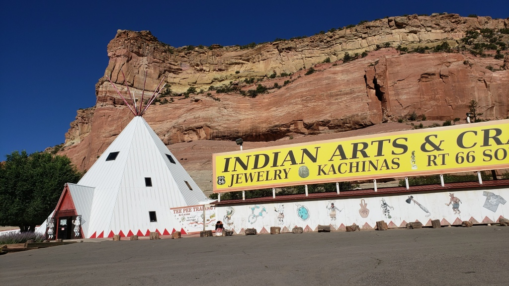 Giant teepee against rock cliff