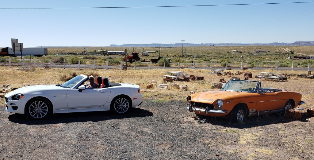 Modern Fiat Spider and antique Spider in weed-smattered parking lot
