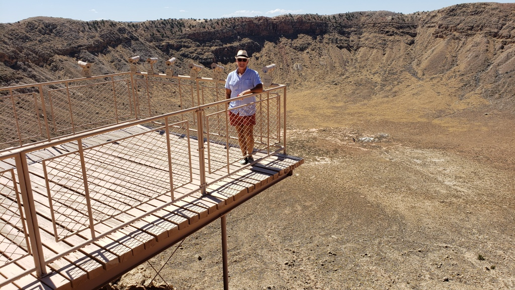 man standing on platform over crater