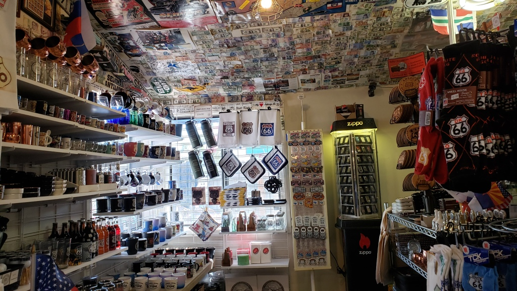 souvenir shop with hundreds of patches and foreign currency bills on ceiling