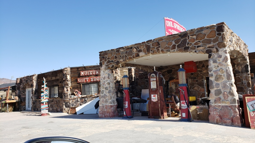 stone building with signs and old gas pumps