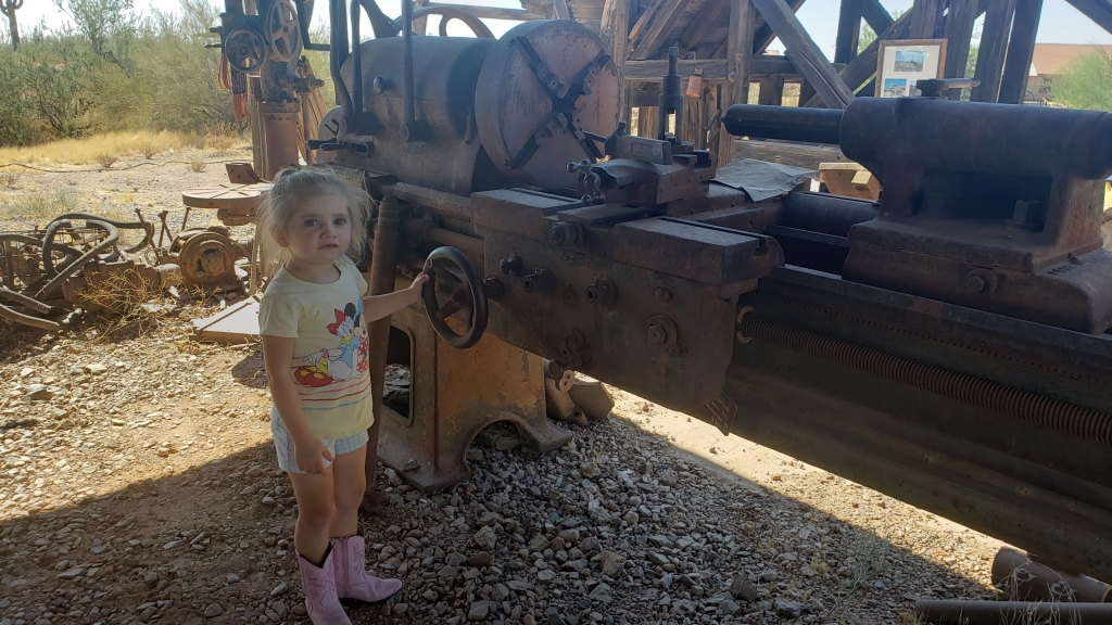 child standing next to abandoned mine equipment