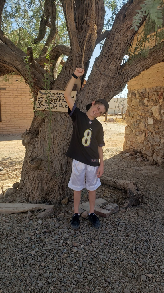boy poses next to hanging tree
